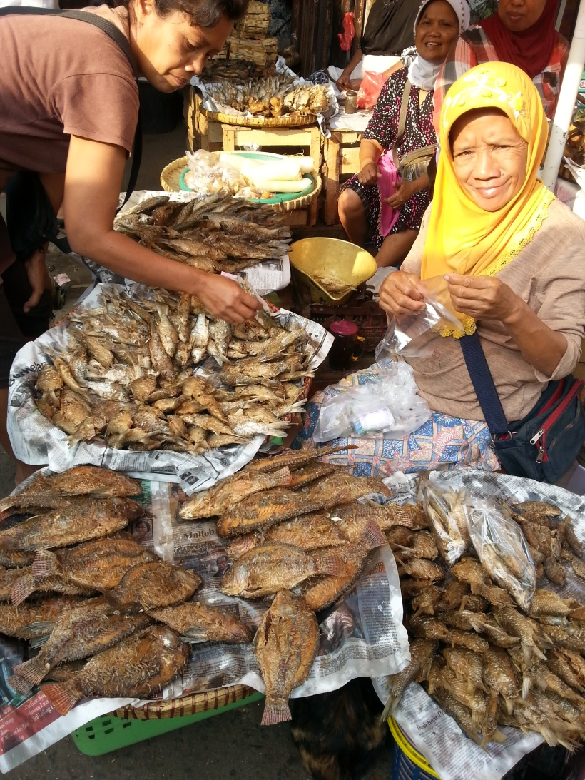 A friendly woman selling dried fish